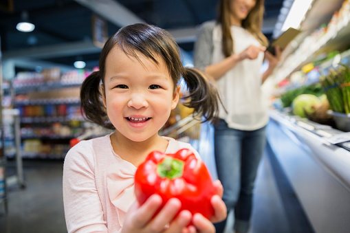 Girl with red pepper in grocery store