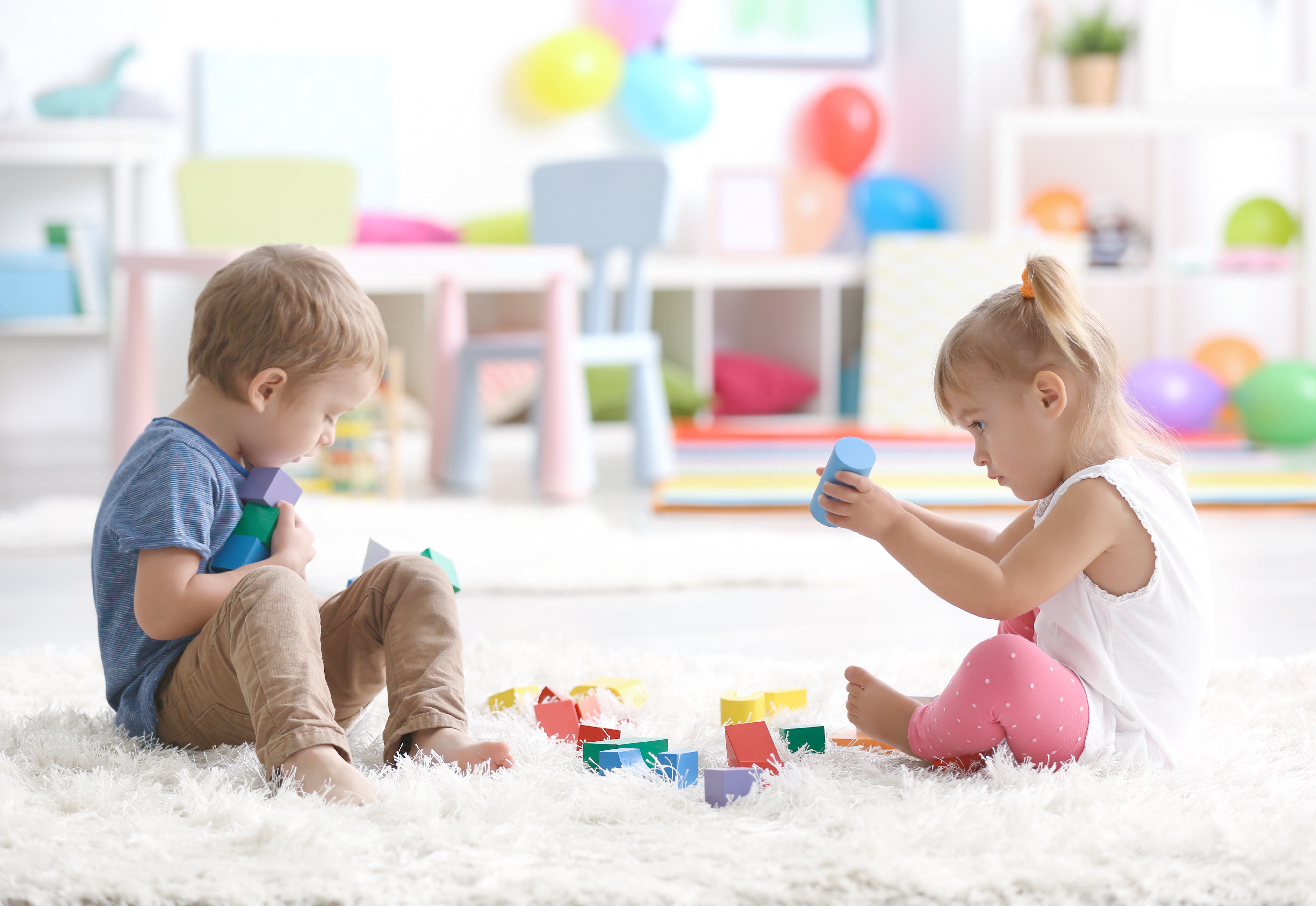 Two small children playing on floor