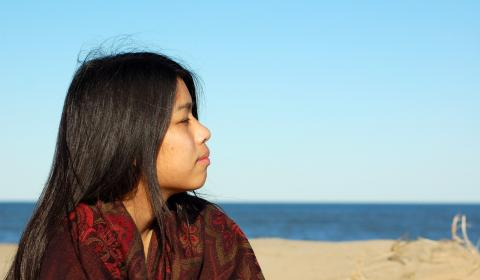 Indigenous girl overlooking water